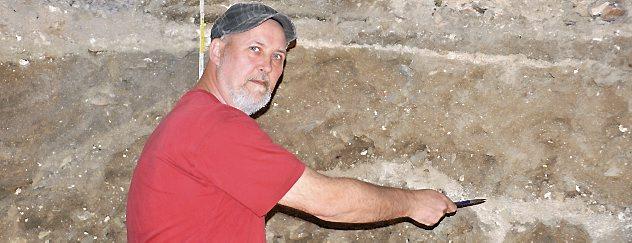 Die Arbeiten in der Arnstädter Oberkirche hat Grabungstechniker Frank Jelitzki vom Landesamt für Denkmalpflege und Archäologie übernommen. Er zeigt auf die Ablagerungsschichten an der Grabungsstelle. Foto: Michael Keller