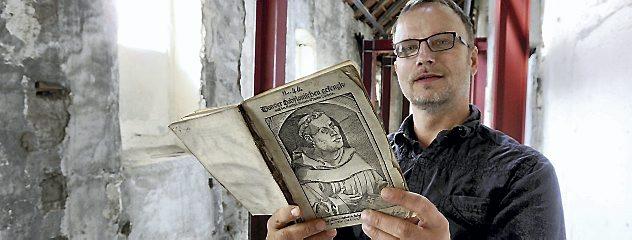 Pfarrer Thomas Kratzer im im Umbau befindlichen Kreuzgang in der Oberkirche Arnstadt mit einem wertvollen Luther-Erstdruck aus dem Jahr 1520. Er soll zum 500. Reformationsjubiläum zu sehen sein. Foto: Hans-Peter Stadermann