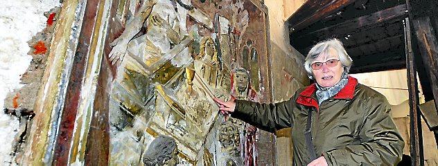 Renate Friedel vom Verein Oberkirche Arnstadt zeigt das Grabdenkmal für Georg Fischer aus dem Jahr 1505. Die Farben sind gut erhalten, die Darstellung sehr detailreich. Foto: Hans-Peter Stadermann