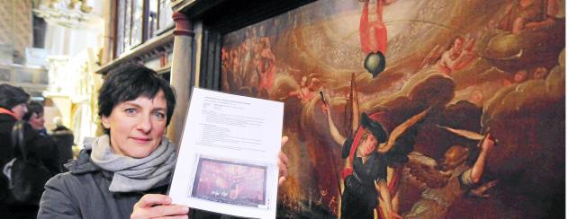 """Susanne Ruda hat vier von zehn stark geschädigten Tafelbildern bereits restauriert. Hier steht sie vorm """"Jüngsten Gericht"""". In der Hand hält sie ein Foto, das den ursprünglichen Zustand des wertvollen Kunstwerks zeigt. Foto: Christoph Vogel"""
